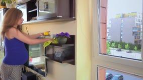 Polvo limpio cuidadoso de la mujer embarazada en sala de estar en casa almacen de metraje de vídeo