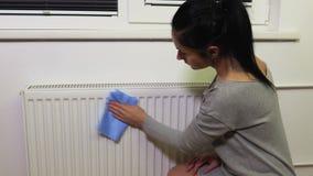 Polvo limpio de la mujer del radiador de calefacción almacen de metraje de vídeo