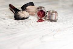 Polvo, pigmentos, brillo, cepillos y lápiz de ojos Fotografía de archivo