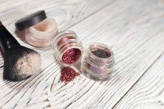 Polvo, pigmentos, brillo, cepillos y lápiz de ojos Imagen de archivo libre de regalías
