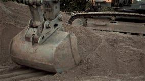 Polvo que trabaja durante obras viales, cierre de Digging Sand And del excavador encima del tiro del cubo de una máquina de excav almacen de video