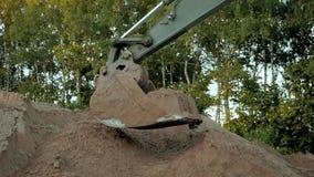 Polvo que trabaja durante obras viales, cierre de Digging Sand And del excavador encima del tiro del cubo de una máquina de excav metrajes