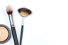 Polvo y cepillos del maquillaje en el fondo blanco Fotos de archivo libres de regalías