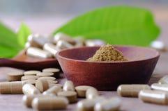 Polvo y medicina herbarios en el cuenco de madera con la hoja en la tabla Imágenes de archivo libres de regalías