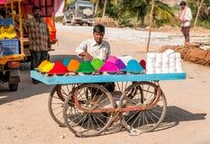 Polvos coloridos del tika de la venta del vendedor ambulante en el mercado callejero de Puttaparthi, la India Imagen de archivo libre de regalías