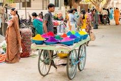 Polvos coloridos del tika de la venta del vendedor ambulante en el mercado callejero de Puttaparthi, la India fotos de archivo