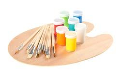 Poly acryldieverf met verschillende kleuren, verfborstels en houten die palet wordt geplaatst, op witte achtergrond worden geïsol royalty-vrije stock foto