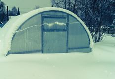 Polycarbonate greenhouse under the snow in winter on the eve of the season stock images