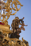 Polychromed figure in a golden throne during a procession of holy week Stock Images