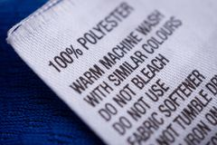 Polyester clothing label with laundry care instructions tag. On blue shirt jersey royalty free stock photos