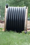 Polyethylene pipes in the coil for gas and water are liyng on the ground. Repair works Royalty Free Stock Photography