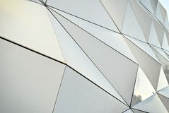 Polygonal triangle glass facade of modern building. Royalty Free Stock Images