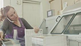 Polygrafprintingprocess - en kvinna talar telefonen och gör manuellt arbete stock video