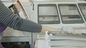 Polygrafprintingprocess - en kvinnas hand avslutar ett papper för en tidskrift arkivfilmer