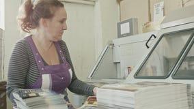 Polygrafprintingprocessen - manuellt arbete - en kvinna avslutar ett papper för en tidskrift arkivfilmer