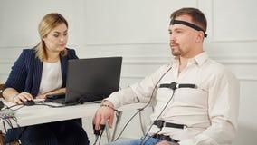 Polygraph de technicus leest vragen van laptop Mens met de leugendetectorkring die wordt verbonden stock foto's