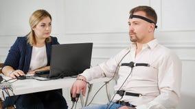 Polygraph de technicus leest vragen van laptop Mens met de leugendetectorkring die wordt verbonden stock foto