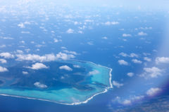Polynesia. The atoll in ocean through clouds. Aerial view. Royalty Free Stock Photo