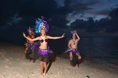 Polynesian Cook Islander dancers dancing on Muril beach lagoon i. Young attractive and exotic Polynesian Cook Islander dancers male and female dancing on Muril Stock Image