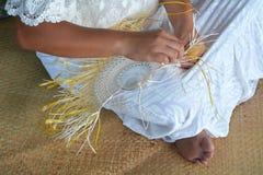 Polynesian Cook Islander woman weaving a hand fan in Rarotonga C. Young attractive and exotic Polynesian Cook Islander woman weaving a hand fan in Rarotonga royalty free stock images