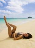 Polynesian girl in a black bikini. A beautiful Polynesian girl in a black bikini lying on a secluded Hawaii beach at the ocean's edge with a plumeria blossom in Royalty Free Stock Photo
