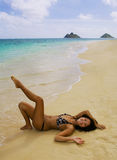 Polynesian girl in a black bikini. A beautiful Polynesian girl in a black bikini lying on a secluded Hawaii beach at the ocean's edge with a plumeria blossom in Stock Photography