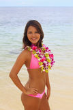 Polynesian girl with flower lei. A beautiful Polynesian girl with flower lei in a pink bikini standing on a secluded Hawaii beach Stock Photo