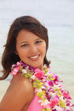 Polynesian girl with flower lei. Portrait of a beautiful Polynesian girl with flower lei in a pink bikini standing on a secluded Hawaii beach Royalty Free Stock Image