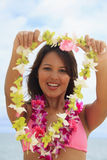 Polynesian girl with flower lei. Portrait of a beautiful Polynesian girl with flower lei in a pink bikini standing on a secluded Hawaii beach offering a lei Stock Photos