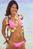 Polynesian girl with flower lei. A beautiful Polynesian girl with flower lei in a pink bikini standing on a secluded Hawaii beach Royalty Free Stock Photography