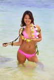 Polynesian girl with flower lei. A beautiful Polynesian girl with flower lei in a pink bikini standing in shallow water by a secluded Hawaii beach Stock Image