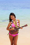 Polynesian girl with flower lei. A beautiful Polynesian girl with flower lei in a pink bikini standing on a secluded Hawaii beach playing an ukulele Royalty Free Stock Photography