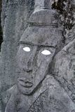 Polynesian male figurine rock carving in basalt sculpture. Carving was an important part of ancient Cook Islands culture, although much of this is lost Royalty Free Stock Photo