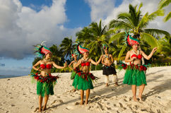 Polynesian Pacific Island Tahitian Dance Group. Group portrait of Polynesian Pacific Island Tahitian dance group in colorful costumes dancing on tropical beach Stock Photo