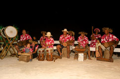 Polynesian Pacific Island Tahitian Music Group. Portrait of Polynesian Pacific Island Tahitian music group in colorful outfit in play music on tropical beach stock photos