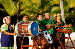 Polynesian Pacific Island Tahitian Music Group. Group portrait of Polynesian Pacific Islanders band plays Tahitian music on tropical beach with palm trees in the Royalty Free Stock Images