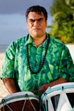 Polynesian Pacific Island Tahitian Music. Portrait of mature Polynesian Pacific islanders man plays Tahitian Music with drums on tropical beach with palm trees Royalty Free Stock Image