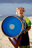 Polynesian Pacific Island Tahitian Music. Portrait of mature Polynesian Pacific islanders woman sing and plays Tahitian Music with drum on tropical beach Stock Photography