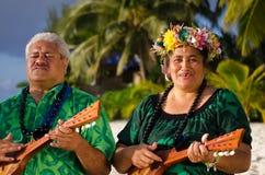 Polynesian Pacific Island Tahitian Music. Portrait of two mature Polynesian Pacific islanders couple sing and plays Tahitian Music with Ukulele guitars on Royalty Free Stock Image