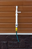 Polypropylene pipe with a tap on siding wall Stock Photos