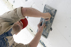 Polystyrene ceiling. A worker installing polystyrene isolation on a ceiling, making the surface smooth. White dust all over the place Stock Photos