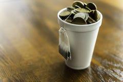 Polystyrenkopp som fylls med mynt och den hängande yttersidan för tepåse arkivbilder