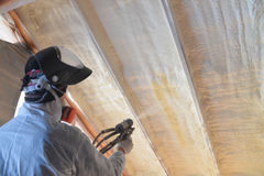 Polyurea Spraying, warming foam coating of roof, focus on wall.  Stock Image