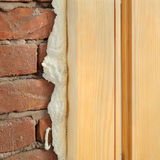 Polyurethane for door or window install. Wooden door or window install, closeup of polyurethane foam wood and bricks royalty free stock photo