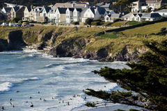 Polzeath, North Cornwall. View of Polzeath from a cliff with surfers in the sea Stock Photo