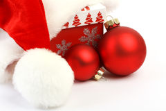 有pom pom的圣诞老人帽子装饰有红色圣诞节装饰的红色圣诞节礼物和在白色背景的两个红色暗淡圣诞节球 免版税图库摄影
