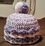 Pom Pom Cap hecho a ganchillo púrpura y rosado de la niña Foto de archivo libre de regalías