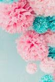 Pom-poms azules y rosados en la pared de ladrillo del fondo Fotos de archivo