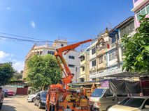 Pom Prap Sattru Phai District, Bangkok, Thailand - 19 March 2018: Electrician on the truck crane shifted up to check and repair stock photography