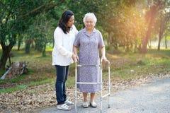 Pomaga Azjatyckiego seniora i dba lub starsza starej damy kobieta u?ywa piechura z silnymi zdrowie przy parkiem podczas gdy chodz obrazy royalty free